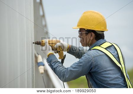 Foreman worker wearing helmet drilling fence wall home by electric drill