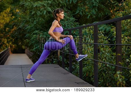 Portrait Of Woman In Sportwear Doing Workout Fitness Stretching On Urban City Background. Female Spo