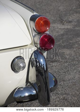 Rear of an old british classic car . Particular view of right tail light and shiny chrome bumper . The car is a model produced between 1955 and 1962