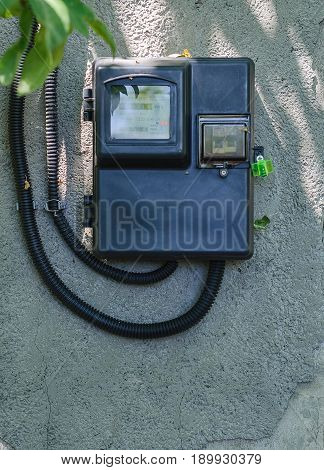 Black electric meter on the wall of the country house.