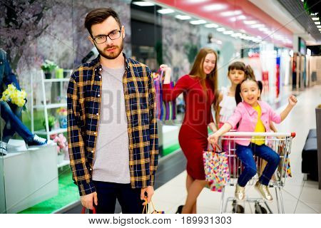 Dad is bored with shopping with his family