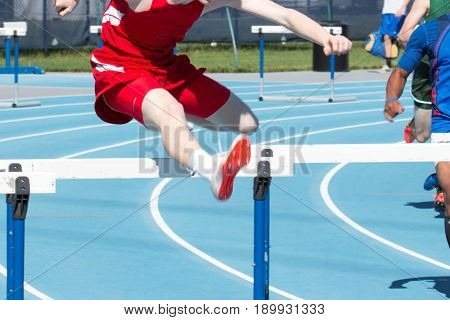 High school boys race the 400 meter intermediate hurdles on a blue track on a sunny day