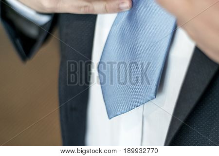 Black suit, white shirt and blue tie. Business, financial or politic concept hands tying up