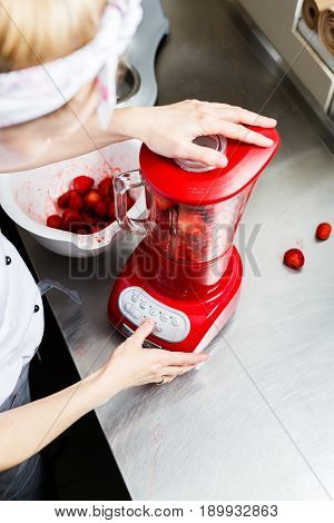 Woman Grind Strawberries In A Red Blender