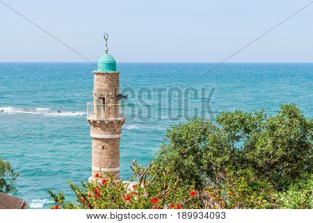 Minaret of the mosque in old Jaffa on blue sky and Mediterranean sea background. Israel.