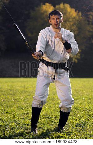 The ninja in white kimono is practicing with nunchaku outdoors.
