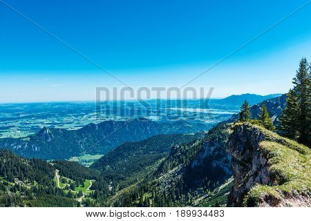 View of lush green alpine scenery from Aggenstein, Germany with forested mountain peaks and valleys stretching into the distance towards Fussen and Forgensee in a scenic landscape