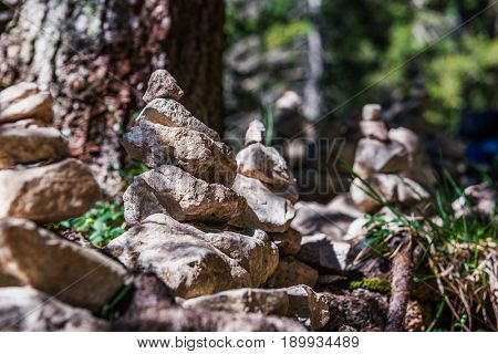 Closeup of balancing rock cairns in countryside with trees in background, summer scene