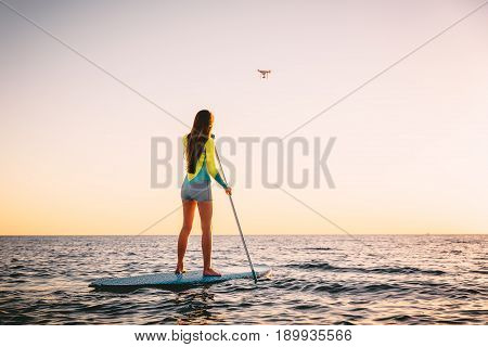 Attractive young woman Stand Up Paddle Surfing and drone copter with beautiful sunset colors