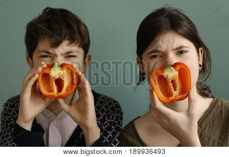 teenager siblings brother and sister with red sweet cut bulgarian paprika pepper funny photo