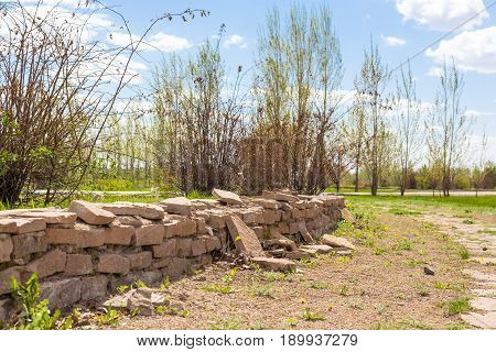 Collapsing A Fence Made Of Stone In A Park Of Astana On A Sunny Day