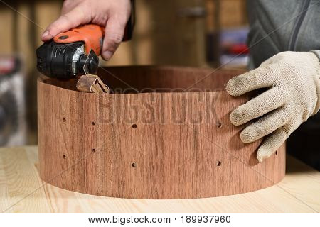 Carpenter grinding wooden drum shell with sandpaper closeup