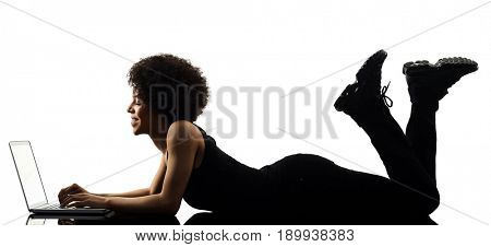 one mixed race african young teenager girl woman computer laptop in studio shadow silhouette isolated on white background