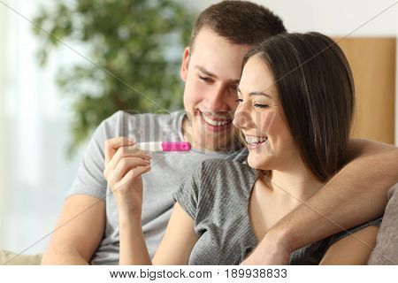 Happy couple checking pregnancy test sitting on a couch in the living room at home