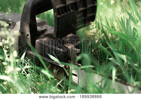 Power saw on green grass on blur background