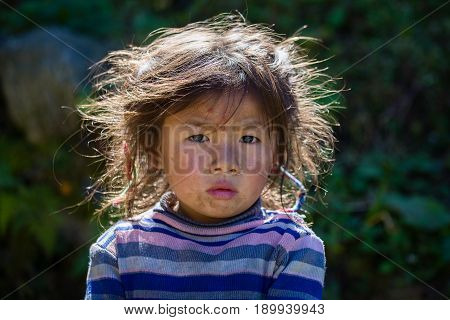 HIMALAYAS ANNAPURNA REGION NEPAL - OCTOBER 14 2016 : Portrait nepalese child on the street in Himalayan village Nepal