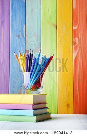 Pencils And Felt-tip Pens With Books On Colourful Wooden Wall