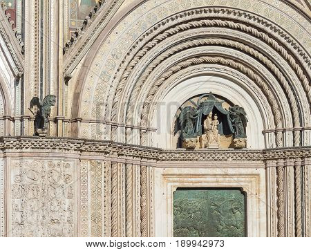 Arch over the bronze door with Madonna and little Jesus in her arms. The upper fragment of the arch with the winged lion over the main entrance door to the Catholic Cathedral of the medieval Gothic style