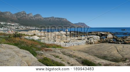 CAMPS BAY, CAPE TOWN, SOUTH AFRICA, HUGE BOULDERS IN THE FORE GROUND WITH A MOUNTAIN IN THE BACK GROUND 24lkoi