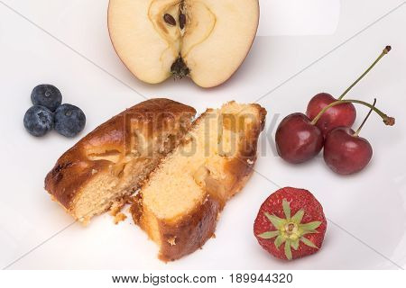 An elongated apple cake with coffee and fruit