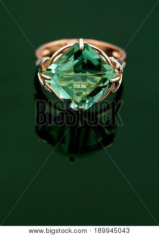 Elegant jewelry ring with emerald on green diamonds with copy space