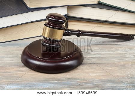 Books and wooden judges gavel on the table in a courtroom office. Law concept.