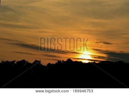 A hazy golden sunset with striking cloud streaks.