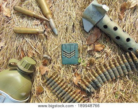 Military rank with ammunition from World War 2 and drinking bottle laying on straw