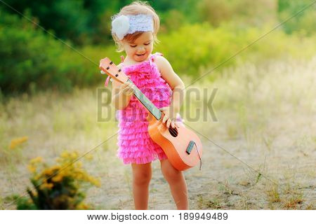 Little girl in pink dress with a toy guitar on background of green bushes. Summer walk baby. Small child celebrating his birthday and playing guitar.