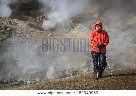 Hiker is standing near boiling springs in Reykjadalur Valley in South Iceland