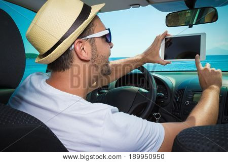 Young car driver touching blank sreen of digital tablet device. Sea in the background. Summer vacation and travel concepts.