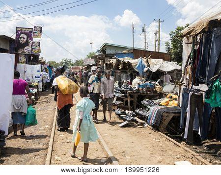 KIBERA, KENYA-NOVEMBER 7, 2015: Unidentified people go about business in the market in Kibera, the largest urban slum in Africa