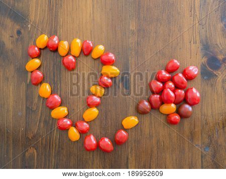 Small Pile of Cherry Tomatoes Linked to a Larger Heart Shaped Pile of Cherry Tomatoes