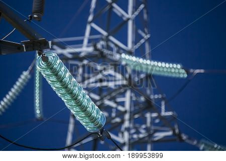 High voltage transmission power tower with glass insulators. Blue sky.