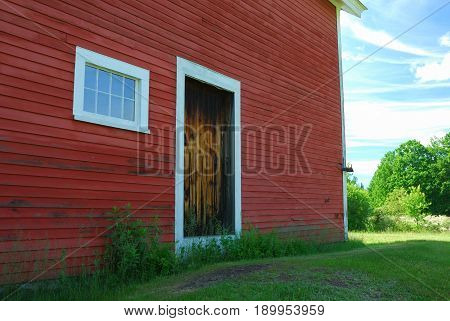 Side of red wooden barn with brown wood door and 8 pane window