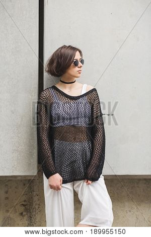 A stylish brunette woman with short hair in white pants and a top with a net. Portrait of a brunette woman. Fashionable young woman wearing choker