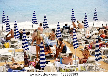 NICE, FRANCE - JUNE 4, 2017: People sunbathing on the beach in Nice, in the French Riviera, France, next to the Promenade des Anglais, the famous seafront walkway of the city