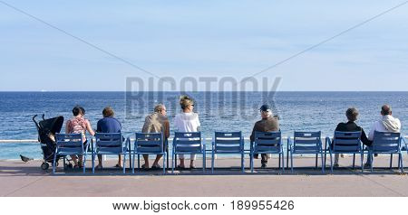 NICE, FRANCE - JUNE 4, 2017: People sitting in the characteristic blue chairs facing the Mediterranean sea at the famous Promenade des Anglais in Nice, in the French Riviera, France