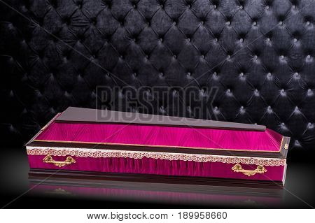 closed wooden color pink coffin isolated on gray luxury background. Pink casket Covered with silk fabric on royal background. Ritual objects for burial.