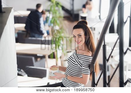 Young gorgeous European woman with pretty face drinking cup of coffee while standing in cozy cafe. Dreamy beautiful female thinking about travel while relaxing in cafe. Looking at camera and smiling