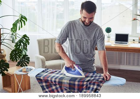 Mid shot of man with charming smile ironing diligently shirt on ironing board