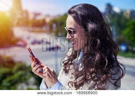 Mid shot of smiling woman surfing on mobile phone on top of building