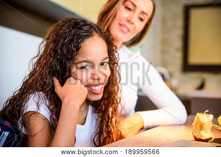 Close up look of a young teenage girl who is sitting at the kitchen table and using a laptop with her parents