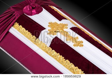 closed coffin covered with red and white cloth decorated with Church gold cross isolated on gray luxury background. Ritual objects for burial. Surrender body dust of the earth. Close-up details.