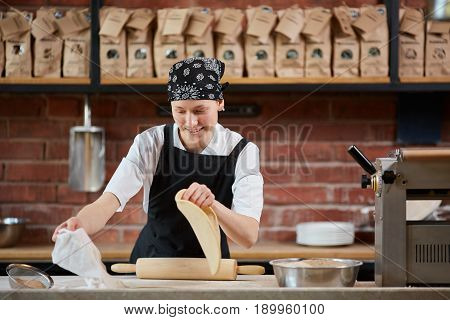 Young female cook with rolling pin working with dough in the restaurant kitchen. Making pasta. Making pasta in restaurant. Woman rolling dough in kitchen