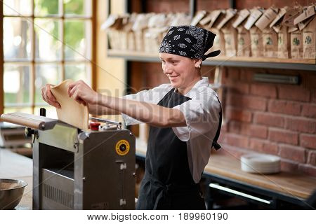 Woman cooks dough on machine for making pasta. Woman rolling dough for pasta. A female making pasta on the counter in the kitchen