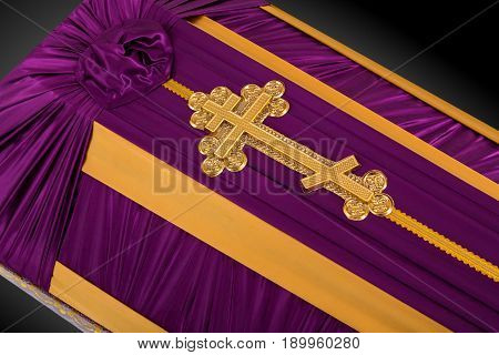 closed coffin covered with purple and beige cloth decorated with Church gold cross isolated on gray luxury background. Ritual objects for burial. Surrender body dust of the earth. Close-up details.