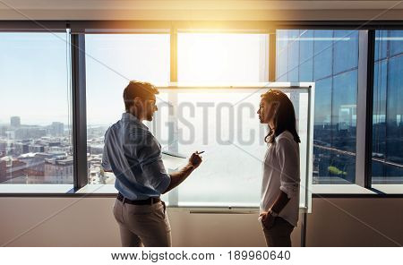 Businessman explaining ideas on whiteboard while a woman listens keenly. Two colleagues discussing business plans in office.