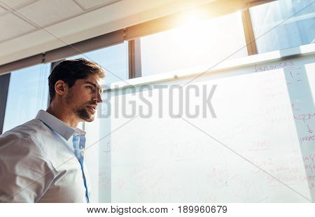 Closeup of businessman against whiteboard in office. Young entrepreneur writing ideas on whiteboard.