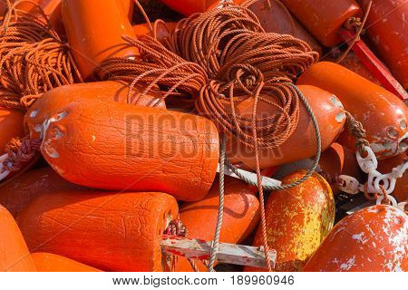 Closeup of multiple orange lobster buoys tied together on a wharf (wharf not visible)